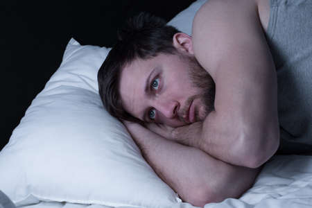 Foto de Young man having sleepless nights because of insomnia - Imagen libre de derechos