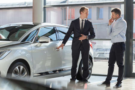 Photo pour Car agent and customer in car showroom - image libre de droit