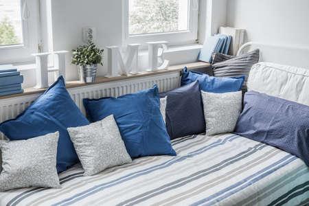 Photo pour White and blue bedding set on the bed - image libre de droit