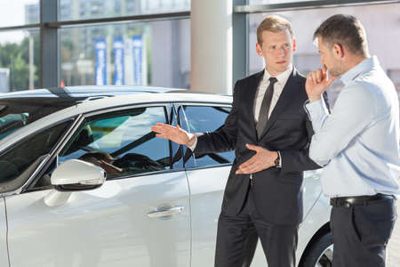 Photo for Car dealer showing vehicle to mature man - Royalty Free Image