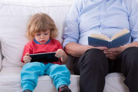 Photo pour Little smart boy learning how to use tablet - image libre de droit