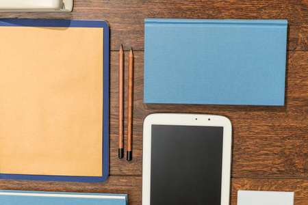 Photo for Tablet, books and papers set on wooden desk office - Royalty Free Image
