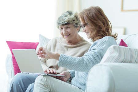 Foto de Picture of kind carer teaching old lady to use laptop - Imagen libre de derechos