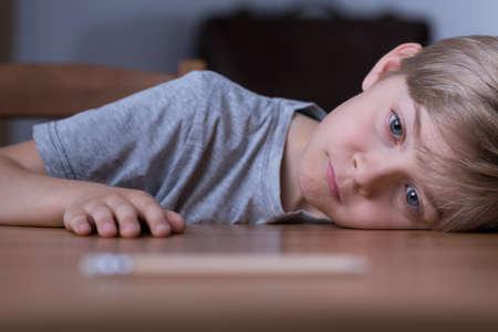 Photo pour Portrait of sad bored boy laying his head on table - image libre de droit