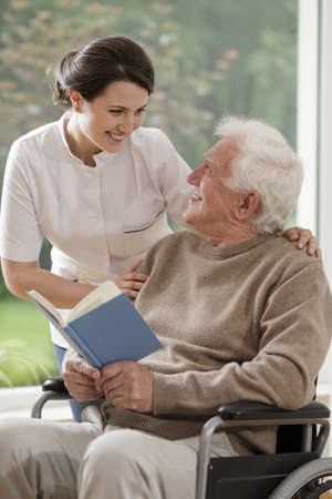 Foto de Caring nurse talking with senior disabled patient - Imagen libre de derechos