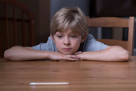 Photo pour Image of small depressed boy laying his head on hands - image libre de droit