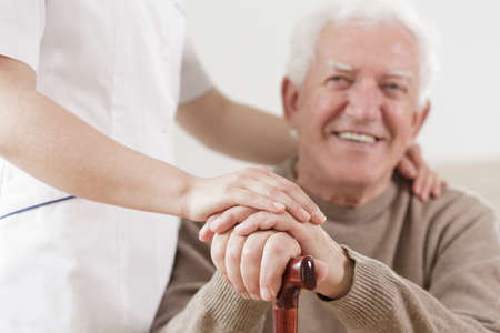 Foto de Smiling senior man and assisting helpful nurse - Imagen libre de derechos