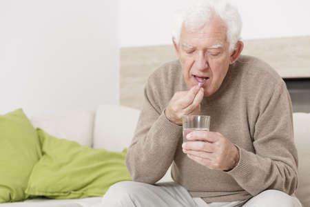 Photo pour Ill senior man taking medicine for hypertension - image libre de droit