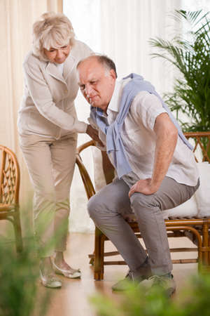 Photo pour Senior man with back pain and his helpful loving wife - image libre de droit