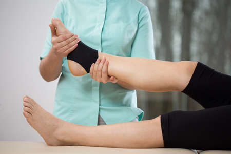 Photo pour Young physiotherapist doing ankle manipulation to elderly woman - image libre de droit