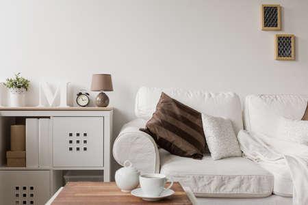 Foto de White couch and commode in drawing room - Imagen libre de derechos