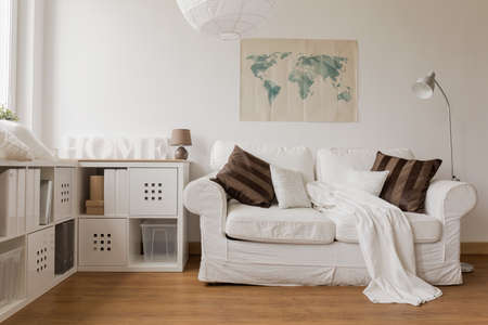 Foto de White sofa and commode in cozy living room - Imagen libre de derechos