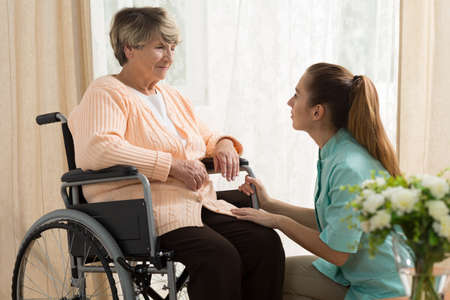Photo pour Picture of caregiver helping old female on wheelchair - image libre de droit