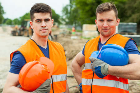 Photo pour Photo of handsome constructive workers holding safety helmets - image libre de droit