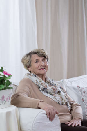 Photo pour Elegant elderly lady sitting on the sofa - image libre de droit
