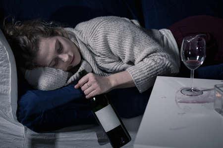 Foto de Tired drunk woman sleeping with bottle of wine - Imagen libre de derechos