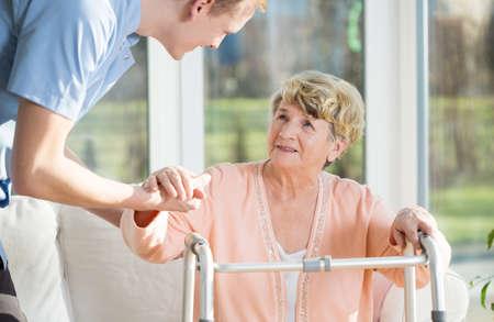 Foto de Man helps to stand up an older woman at nursing home - Imagen libre de derechos