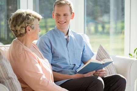 Photo pour Young man reading book with elderly woman - image libre de droit