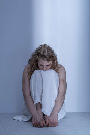 Foto de Curled up scared rape victim in empty room - Imagen libre de derechos