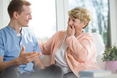 Foto de Happy young man and elderly woman are laughing - Imagen libre de derechos