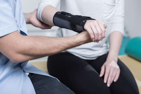 Photo pour Woman using wrist immobiliser after hand's injury - image libre de droit