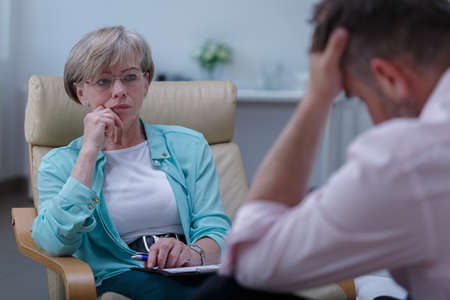 Photo for Photo of professional female therapist listening to male patient - Royalty Free Image