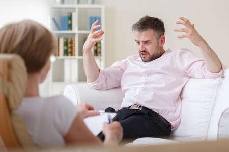 Photo pour Image of upset male patient during psychotherapy session - image libre de droit