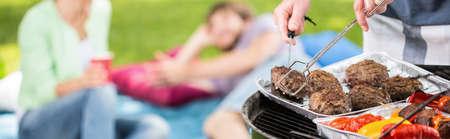 Foto de Panorama of man grilling meat and vegetables for outdoor dinner - Imagen libre de derechos