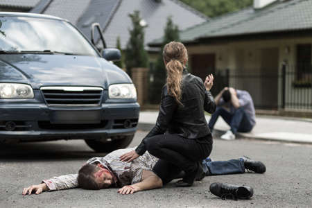 Photo for Bloody victim of car accident lying on the street - Royalty Free Image