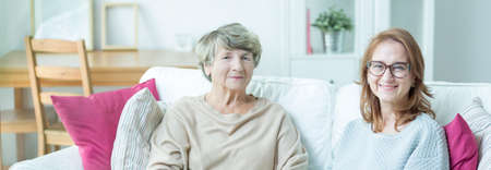 Photo for Elder lady with carer sitting on a couch - Royalty Free Image