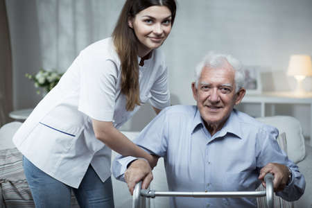 Foto de Nurse helping disabled senior man with standing - Imagen libre de derechos
