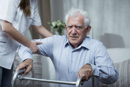 Photo for Physiotherapist helping disabled senior man with standing - Royalty Free Image