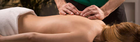 Foto de Young woman having acupressure treatment for back pain - Imagen libre de derechos