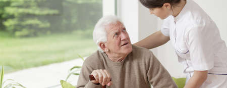 Photo pour Nurse helping senior man in rest home - image libre de droit