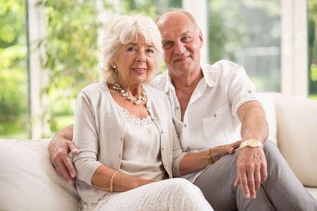 Photo pour Amorous senior couple sitting on the sofa - image libre de droit