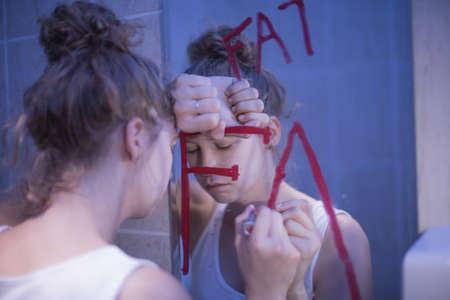 Foto de Picture of bulimic girl and red writing fat on mirror - Imagen libre de derechos
