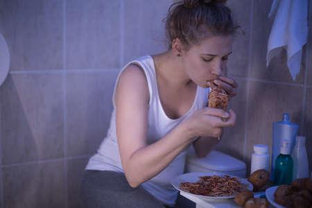 Foto de Photo of girl with bulimia can not control her hunger - Imagen libre de derechos