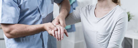 Photo for Male physiotherapist is massaging female patient hand - Royalty Free Image