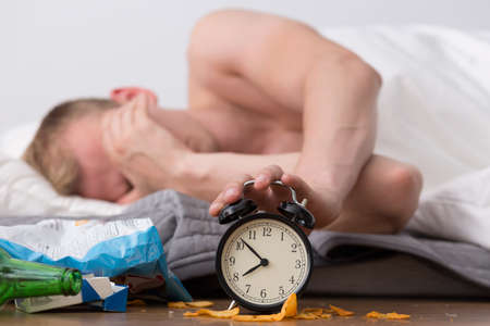 Foto de Man with hangover is waking up and shutting off alarm - Imagen libre de derechos
