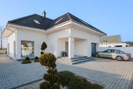 Photo pour Big white residence with garage for new silver car - image libre de droit