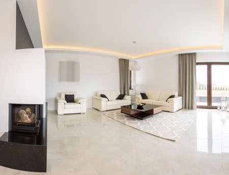 Foto de Spacious bright living room with fireplace and marble floor - Imagen libre de derechos