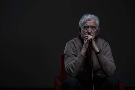 Photo pour Thoughtful elder man sitting in a dark room - image libre de droit