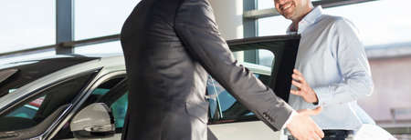 Photo pour Panoramic view of young elegant man getting into the car - image libre de droit