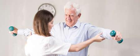 Photo pour Senior man exercising with dumbbells during home rehabilitation - image libre de droit