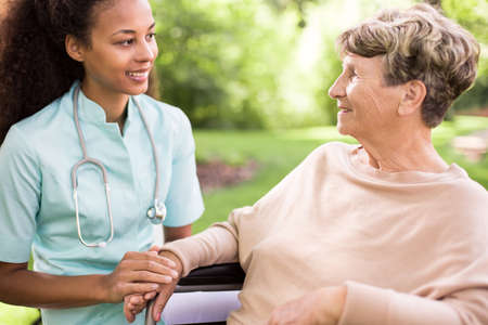 Foto de Senior woman and doctor spending time in the garden - Imagen libre de derechos