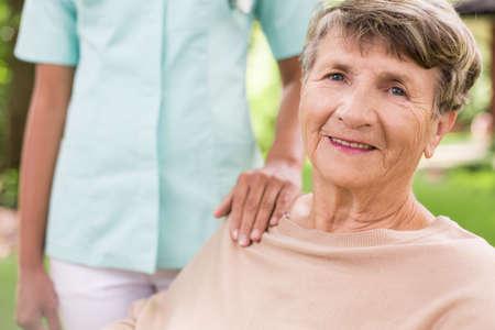 Foto de Senior woman and caring nurse in the garden - Imagen libre de derechos