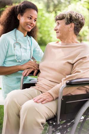 Foto de Disabled woman and caring doctor in the garden - Imagen libre de derechos