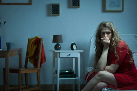 Foto de Nervous girl sitting on the bed and biting nails - Imagen libre de derechos