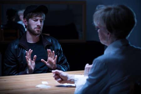 Photo pour Junkie man interrogated by policewoman in a dark room - image libre de droit