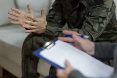 Photo pour Soldier sitting on the sofa during psychological therapy - image libre de droit